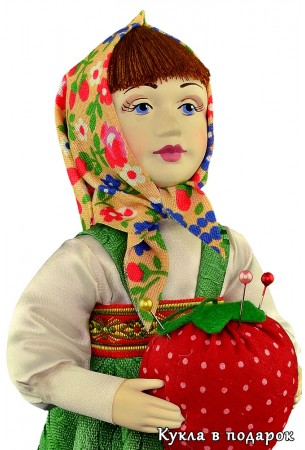 Ягода клубники в руках куклы игольницы